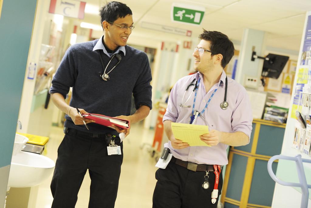 West Suffolk Hospital, Two male junior doctors talking in hospital corridor.