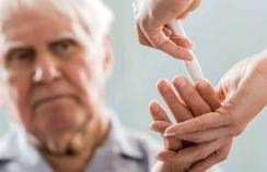 older person taking a blood glucose test