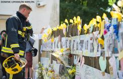 A firefighter reads tributes to those who died in the Grenfell Tower fire