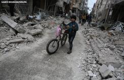 A child walking among the rubble in damage caused by Syrian forces' missile strikes in Eastern Ghouta