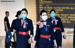 Air crew arrive at Brisbane airport wearing face masks