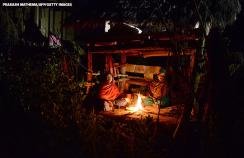 Nepalese women sit by a fire as they live in a Chhaupadi hut during their menstruation period