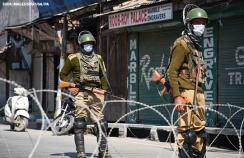 Indian paramilitary troopers wearing protective masks stand on guard in Kashmir in