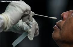 A health worker conducts a swab test to a suspected covid-19 patient