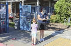 A child is checked in outside her school