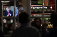 People in a pub watch Boris Johnson on the TV