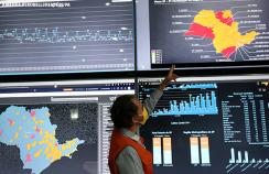 A researcher in Brazil points to a screen showing data on covid-19