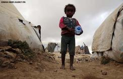 A child walks outside his family's shelter at Khamer displaced camp in Amran province, Yemen