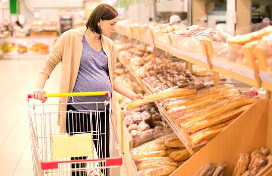 A pregnant woman buying bread