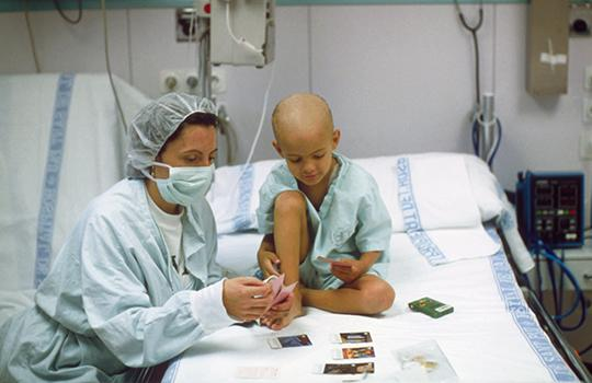 A child with leukaemia plays cards with their mother in hospital