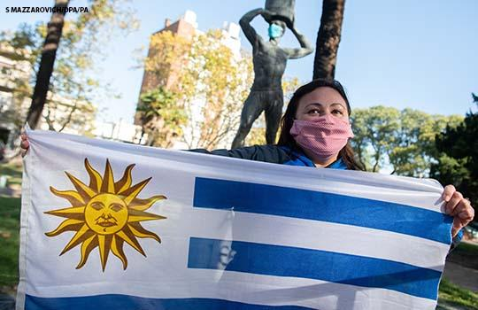 A woman with a face mask holds Uruguay's flag